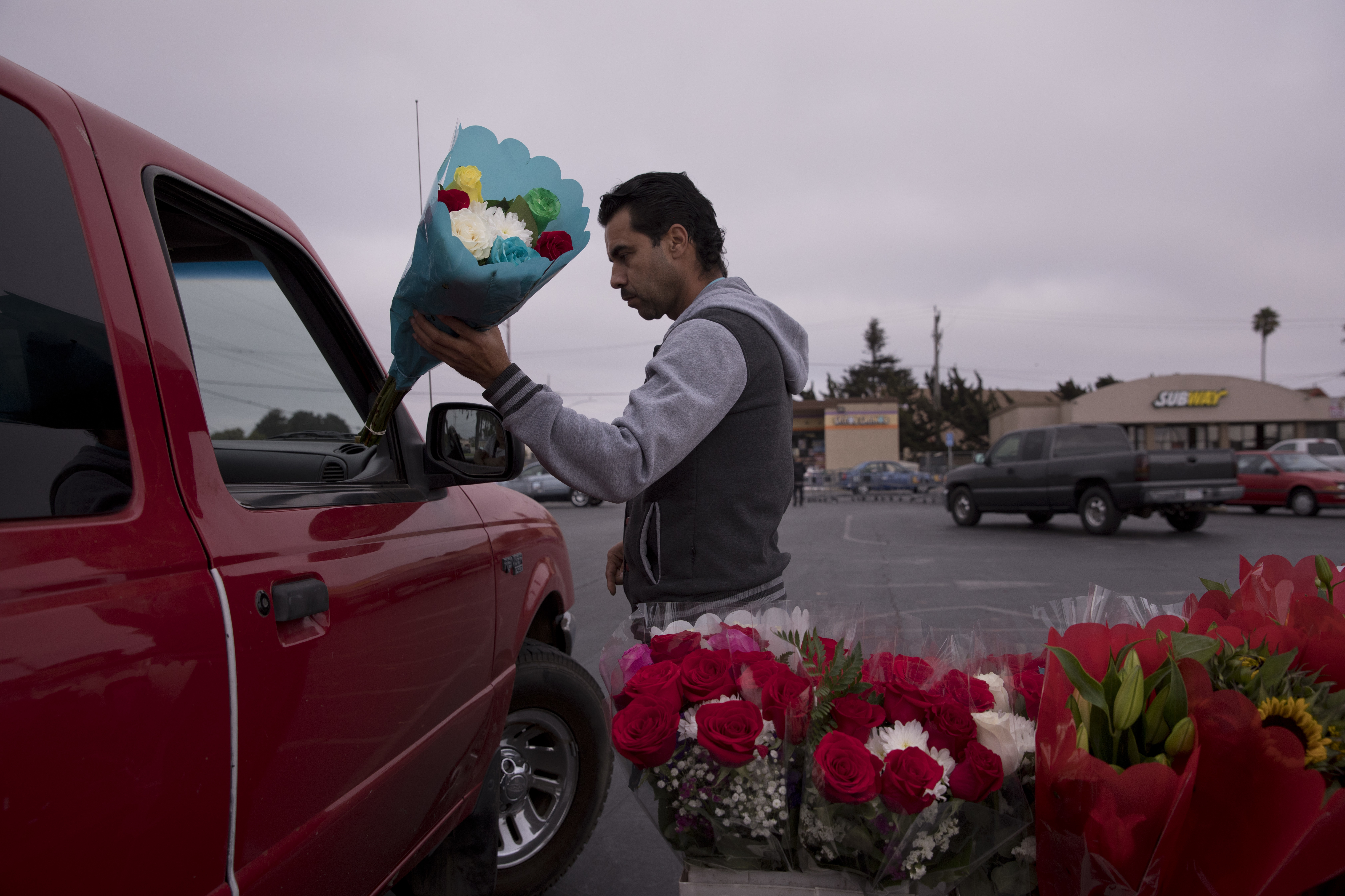 In this Tuesday, Sept. 4, 2018, photo, Jose Contrares, who shares an apartment with seven people, sells flowers in the parking lot of a strip mall in Salinas, Calif. Few cities exemplify California's housing crisis better than Salinas, an hour's drive from Silicon Valley and surrounded by farm fields. It's one of America's most unaffordable places to live, and many residents believe politicians lack a grip on the reality of the region's housing crisis. (AP Photo/Jae C. Hong)