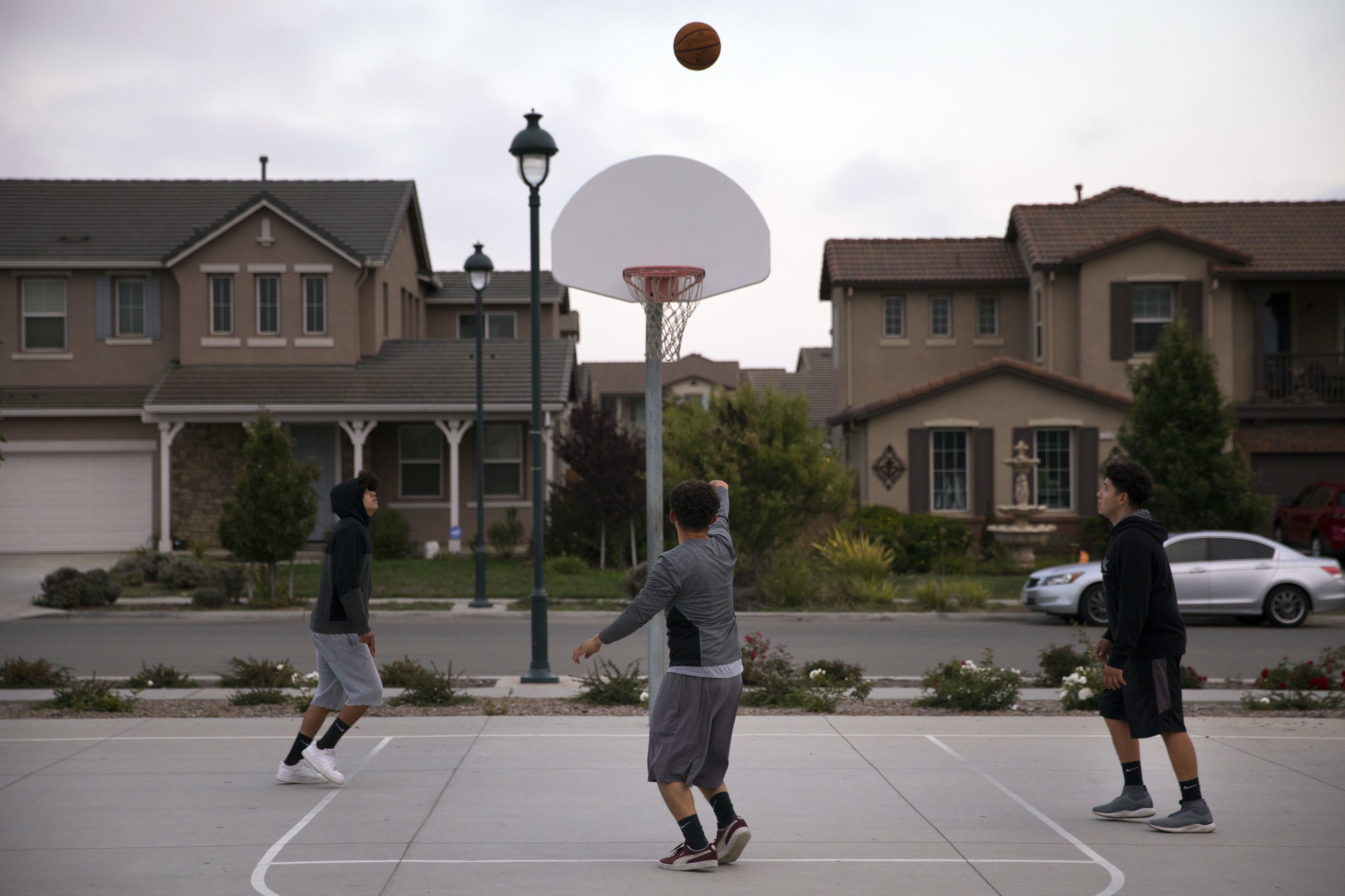 In this Monday, Sept. 3, 2018, photo, three men play basketball at a park in front of newly built homes in Salinas, Calif. Salinas is an affordable location compared to Silicon Valley, where median home prices are about $1 million, but with a less-wealthy population and a median home price that has ballooned to about $550,000 it's one of the least affordable places in America. (AP Photo/Jae C. Hong)