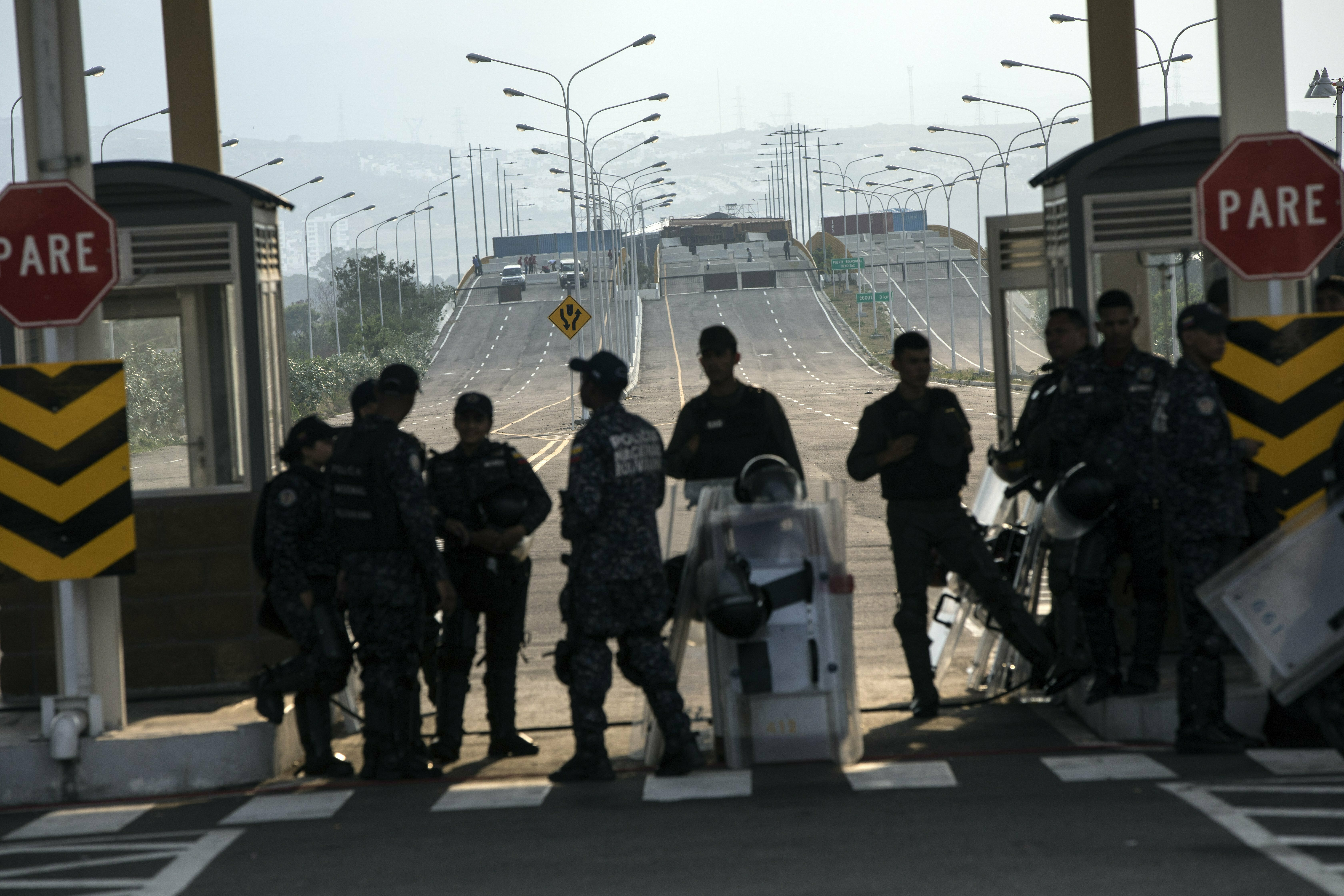 Policemen stand guard during a concert at Tienditas International Bridge, in Venezuela, Friday, Feb. 22, 2019, on the border with Colomcia. Venezuela's power struggle is set to convert into a battle of the bands Friday when musicians demanding Nicolas Maduro allow in humanitarian aid and those supporting the embattled leader's refusal sing in rival concerts being held at both sides of a border bridge where tons of donated food and medicine are being stored. (AP Photo/Rodrigo Abd)