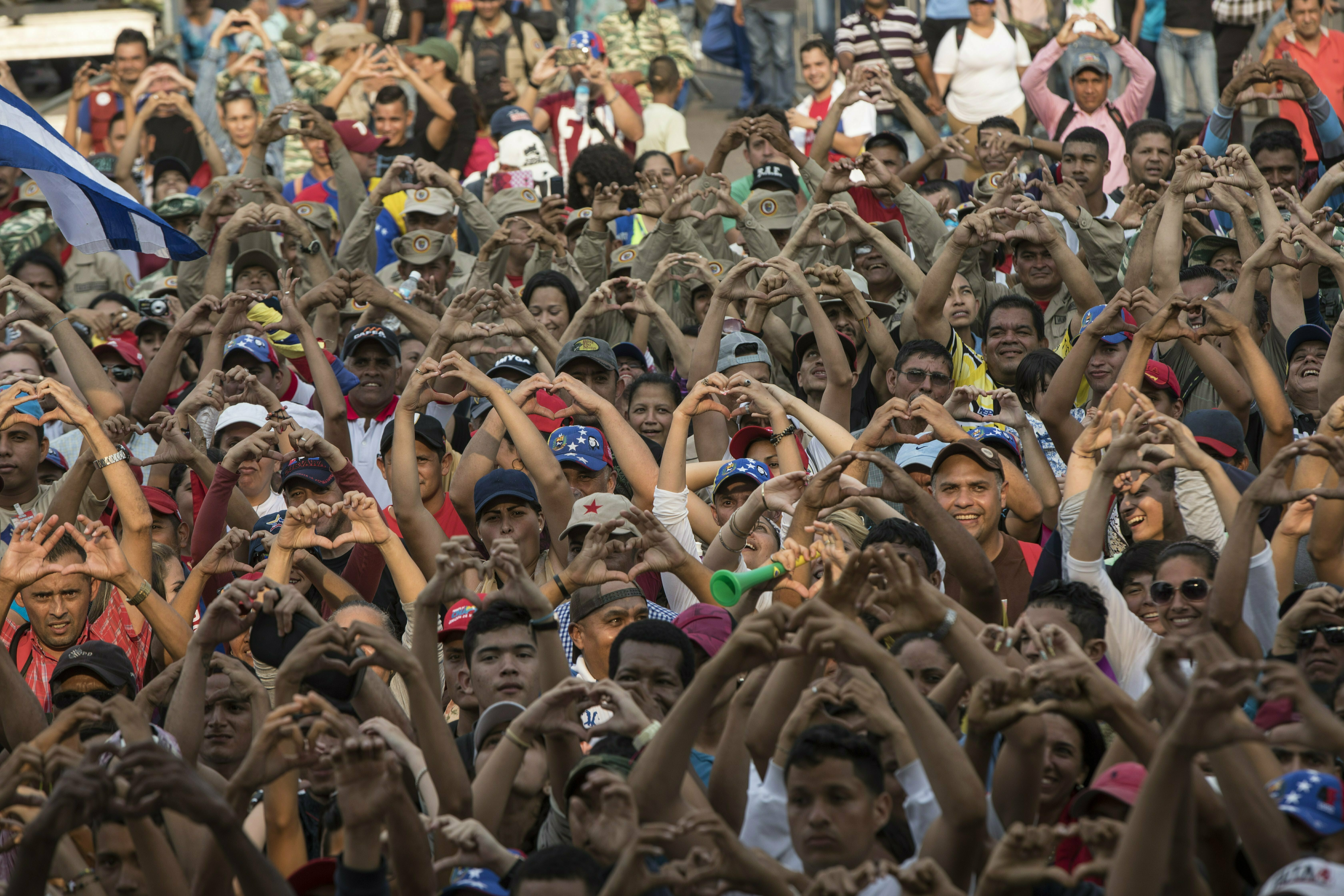 """Government supporters flash heart-hand signals during the """"Hands off Venezuela"""" concert at the Tienditas International Bridge, in Venezuela on the border with Colombia, Friday, Feb. 22, 2019. Venezuela's power struggle is set to convert into a battle of the bands Friday when musicians demanding Nicolas Maduro allow in humanitarian aid and those supporting the embattled leader's refusal sing in rival concerts being held at both sides of a border bridge where tons of donated food and medicine are being stored. (AP Photo/Rodrigo Abd)"""