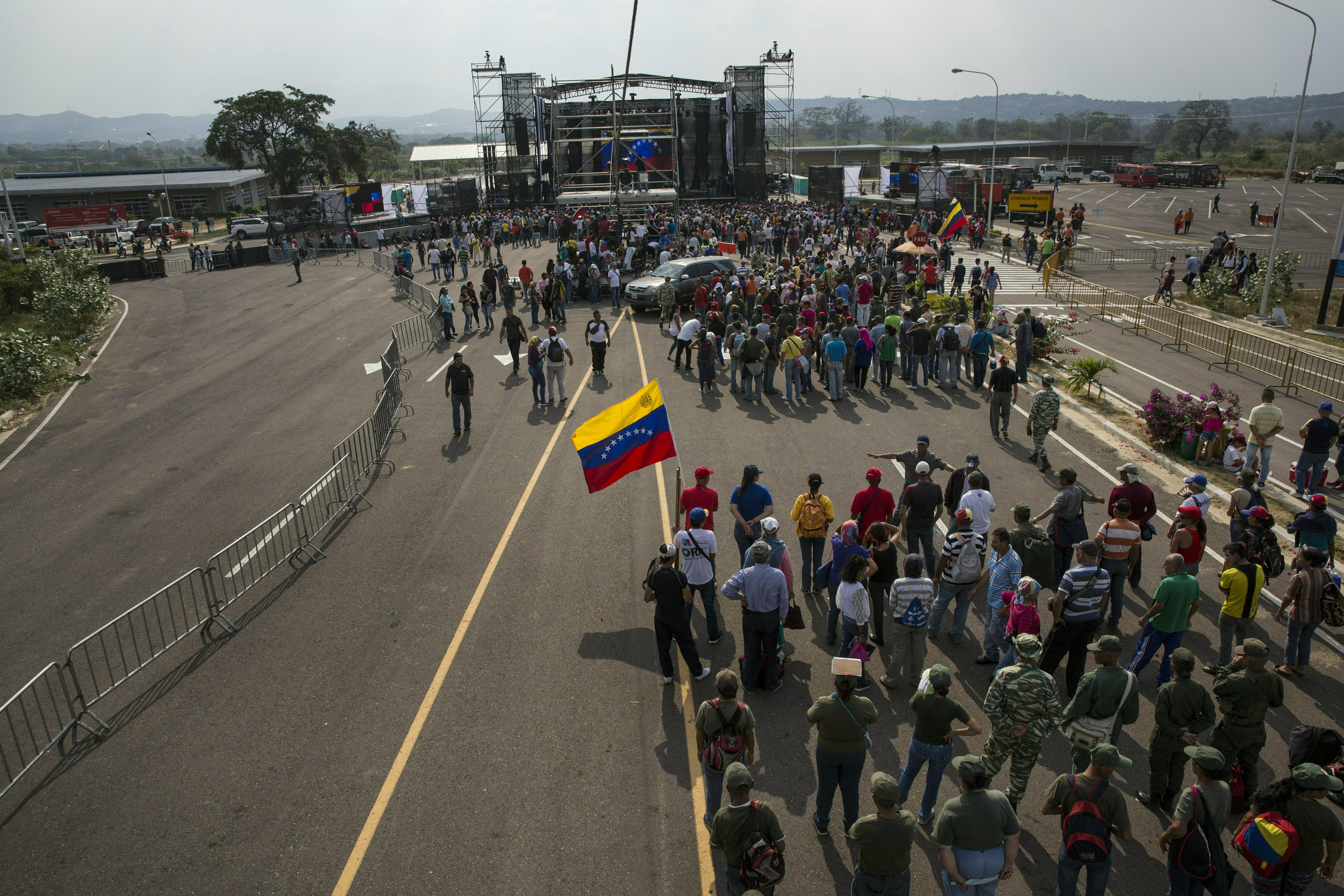 """Government supporters gather during the first day of the """"Hands off Venezuela"""" three-day music festival at the Tienditas International Bridge, in Urena, Venezuela, Friday, Feb. 22, 2019, on the border with Colombia. Venezuela's power struggle is set to convert into a battle of the bands Friday when musicians demanding Nicolas Maduro allow in humanitarian aid and those supporting the embattled leader's refusal sing in rival concerts being held at both sides of a border bridge where tons of donated food and medicine are being stored. (AP Photo/Rodrigo Abd)"""
