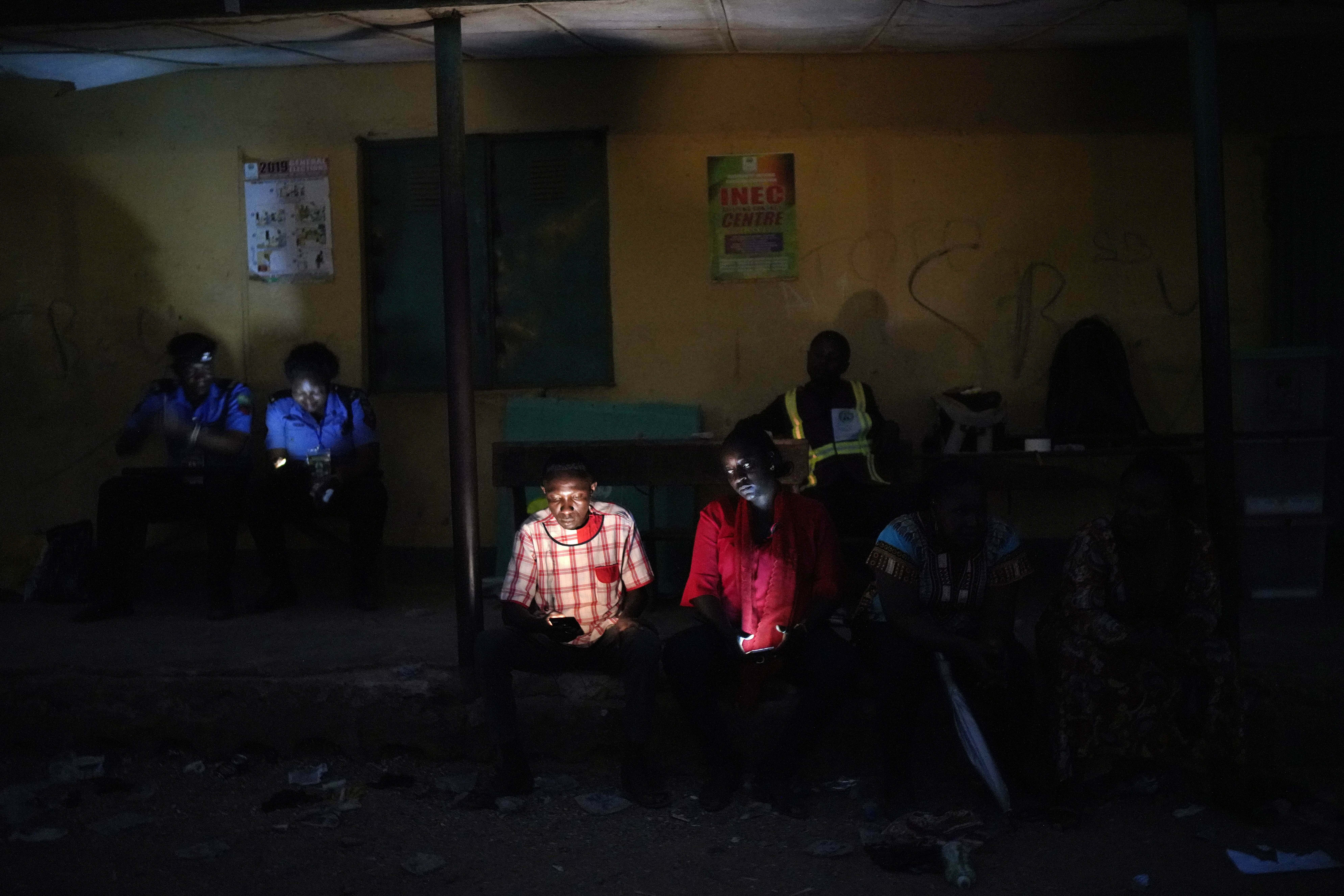 Nigerian election volunteers and police wait for votes to finish being counted in Kaduna, Nigeria, Saturday Feb. 23, 2019. Incumbent President Muhammadu Buhari is facing opposition presidential candidate Atiku Abubakar in the presidential election. (AP Photo/Jerome Delay)