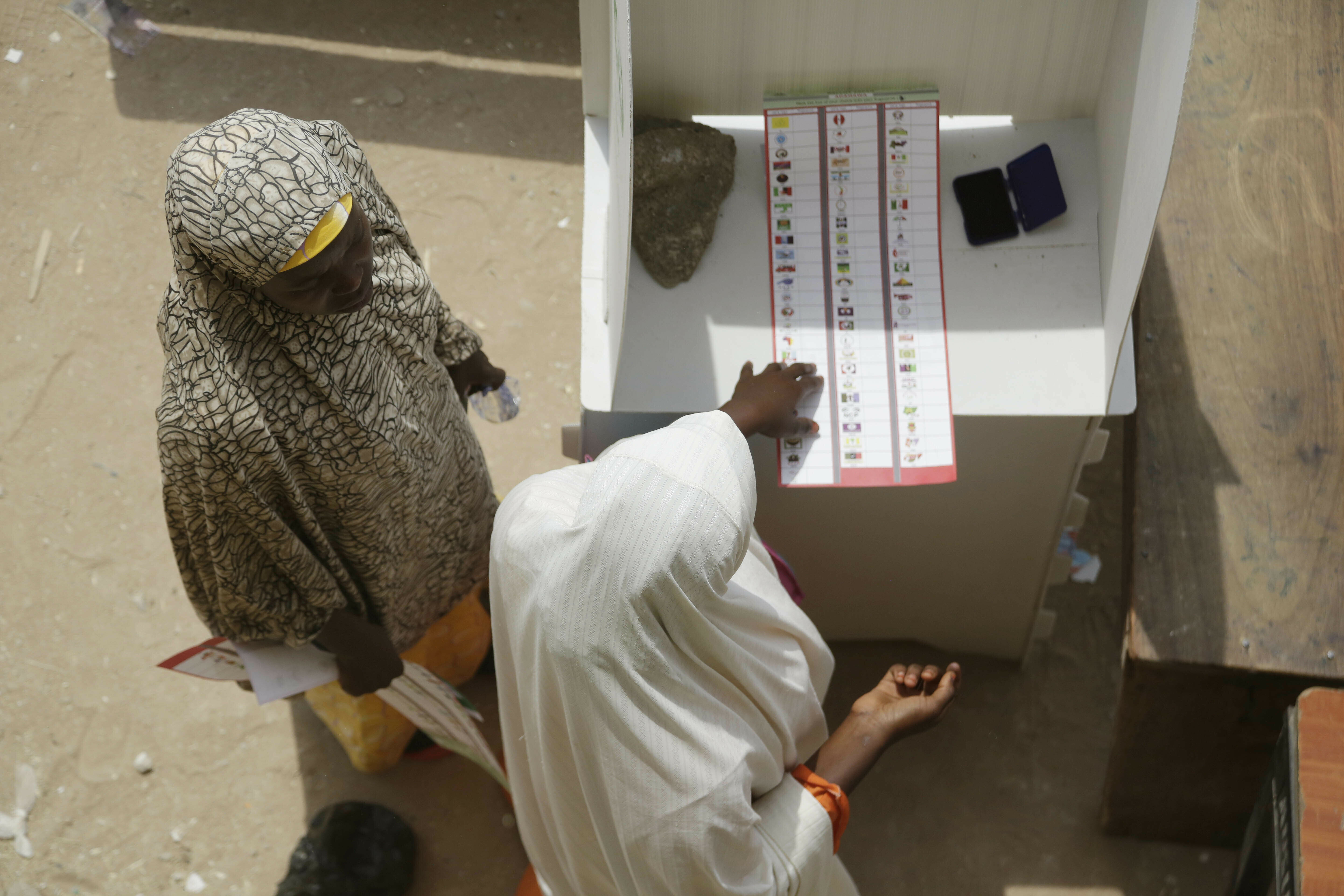 """A woman thumbprints the ballot paper before casting her vote during the Presidential and National Assembly election in Damilu Yola, Nigeria, Saturday, Feb. 23, 2019. Nigerians have waited impatiently for this election, after it was delayed because of logistical """"challenges,"""" just hours before polls were set to open, but now the people get their chance to choose their leaders.(AP Photo/Sunday Alamba)"""