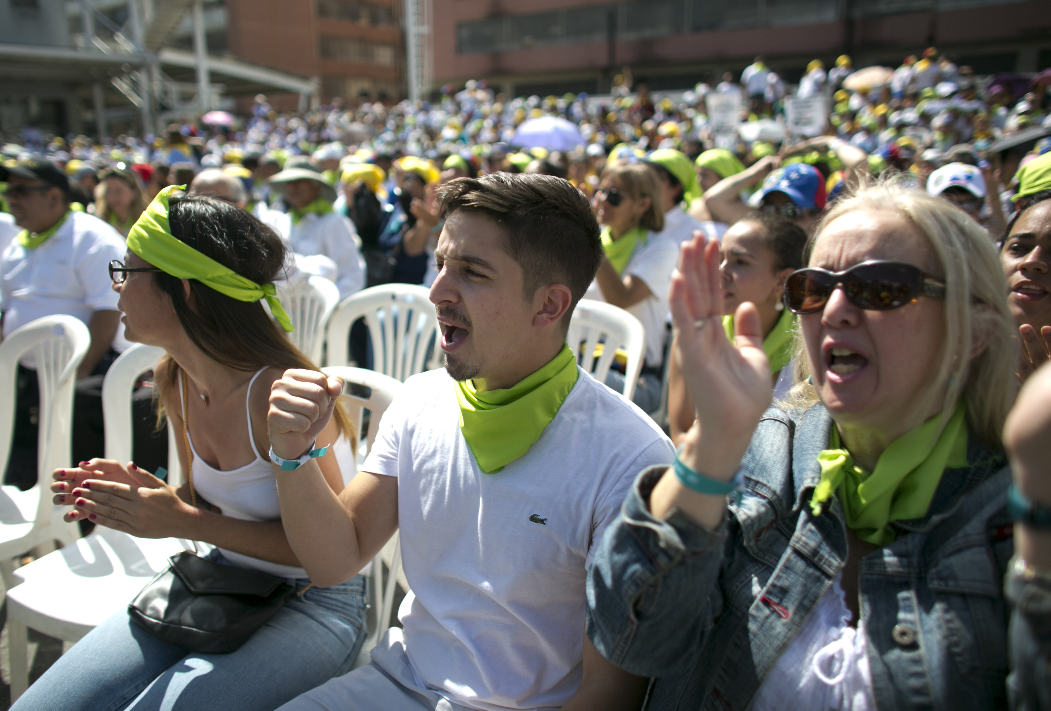 """People scream """"Humanitarian aid!"""" during an event to swear in nurses, doctors, professionals and others, as the group that will help with the arrival and distribution of humanitarian aid in Venezuela, in Caracas, Venezuela, Saturday, Feb. 16, 2019. The U.S. Air Force has begun flying tons of aid to a Colombian town on the Venezuelan border as part of an effort meant to undermine socialist President Nicolas Maduro. The first of three C-17 cargo planes has flown from Homestead Air Reserve Base in Florida and landed in the town of Cucuta.(AP Photo/Ariana Cubillos)"""
