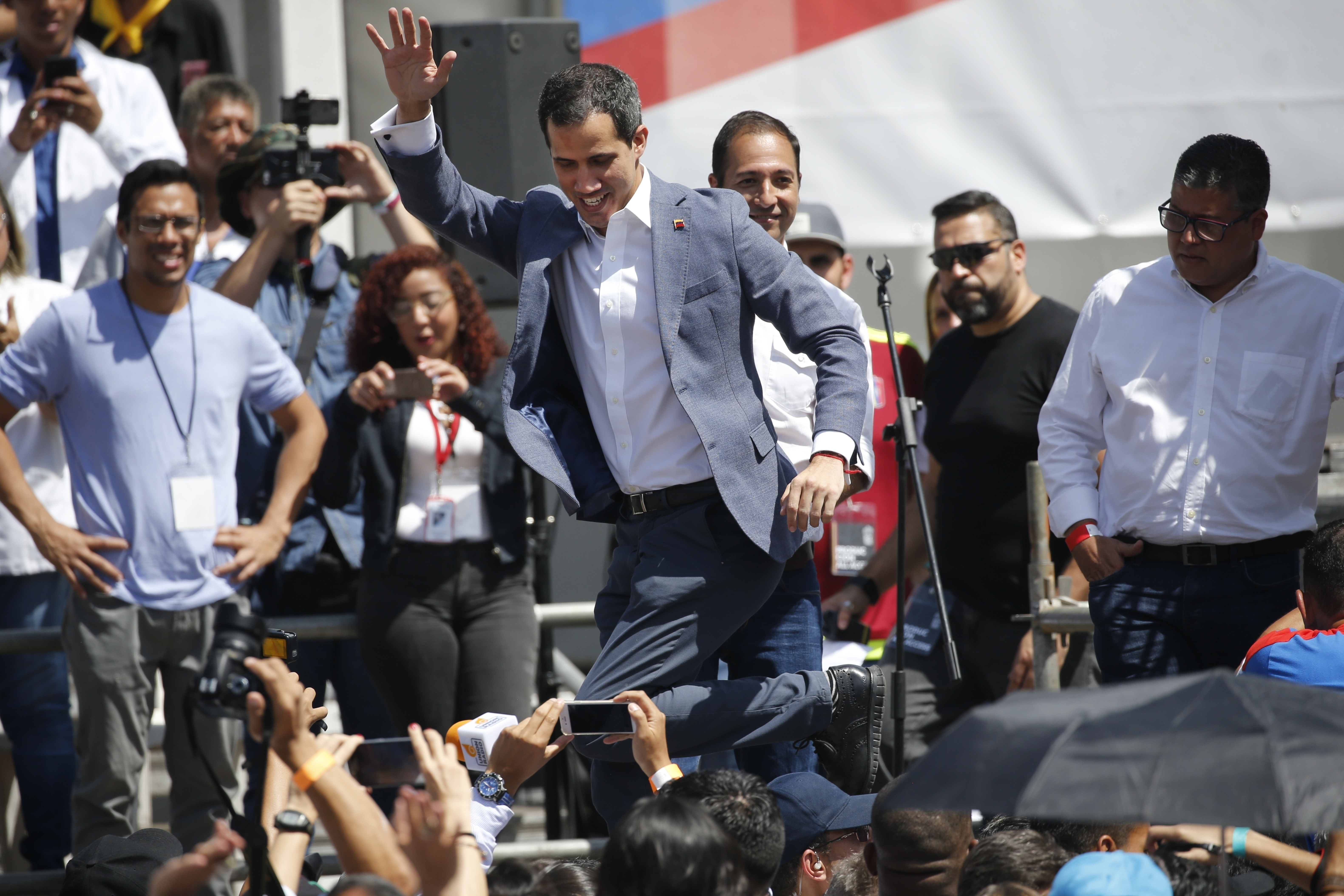 Venezuela's self-proclaimed interim president Juan Guiado greets the crowd after climbing onstage, during an event to swear in nurses, doctors, professionals and others, as the group that will help with the arrival and distribution of humanitarian aid in Venezuela, in Caracas, Venezuela, Saturday, Feb. 16, 2019. The U.S. Air Force has begun flying tons of aid to a Colombian town on the Venezuelan border as part of an effort meant to undermine socialist President Nicolas Maduro. The first of three C-17 cargo planes has flown from Homestead Air Reserve Base in Florida and landed in the town of Cucuta. (AP Photo/Ariana Cubillos)