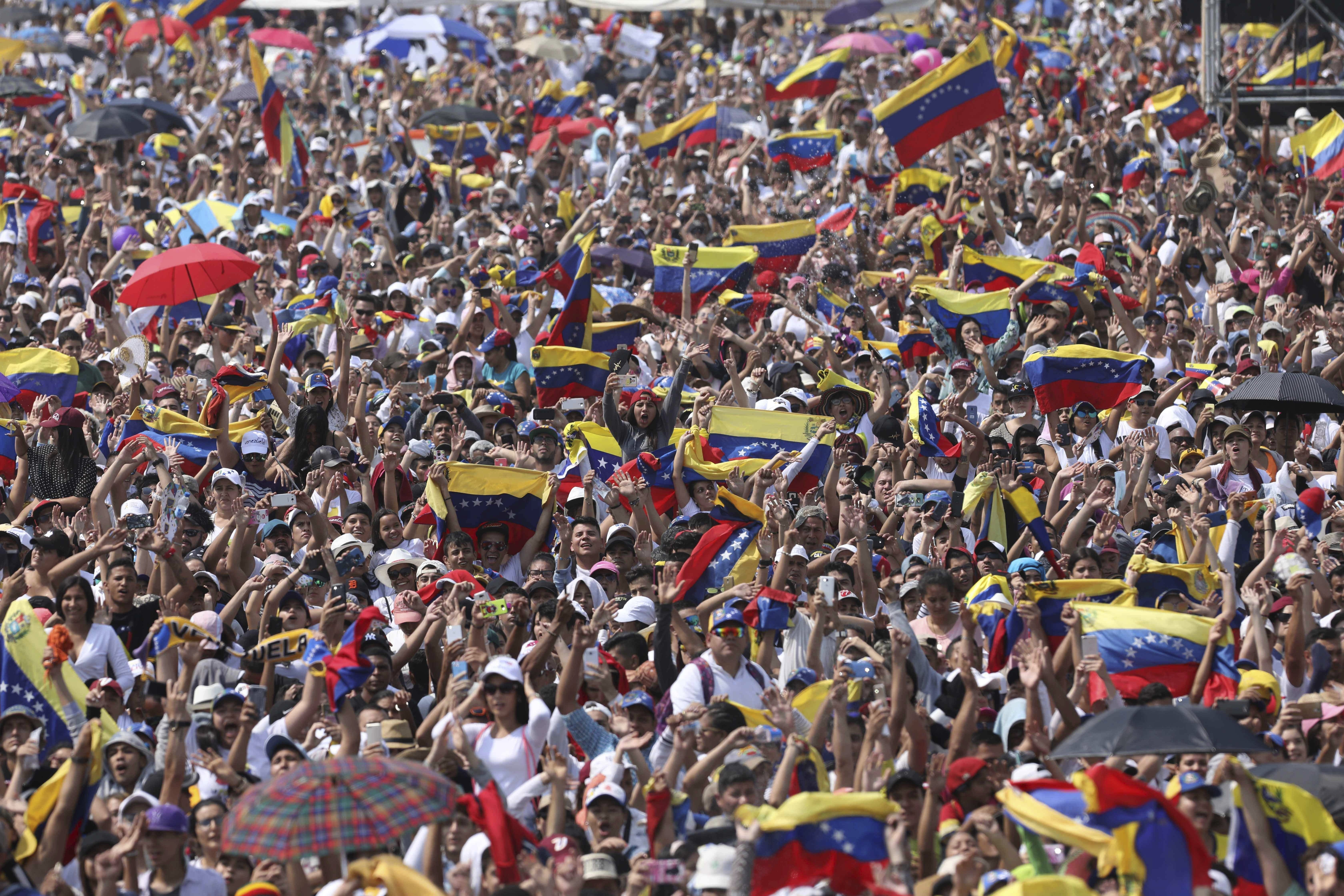 Concert goers unfurl their Venezuelan flags during the Venezuela Aid Live concert on the Colombian side of the Tienditas International Bridge near Cucuta, Colombia, on the border with Venezuela Friday, Feb. 22, 2019. Venezuela's power struggle is set to become a battle of the bands Friday when musicians demanding President Nicolas Maduro allow in humanitarian aid and those supporting his refusal sing in rival concerts being held at both sides of a border bridge where tons of donated food and medicine are stored. (AP Photo/Fernando Vergara)