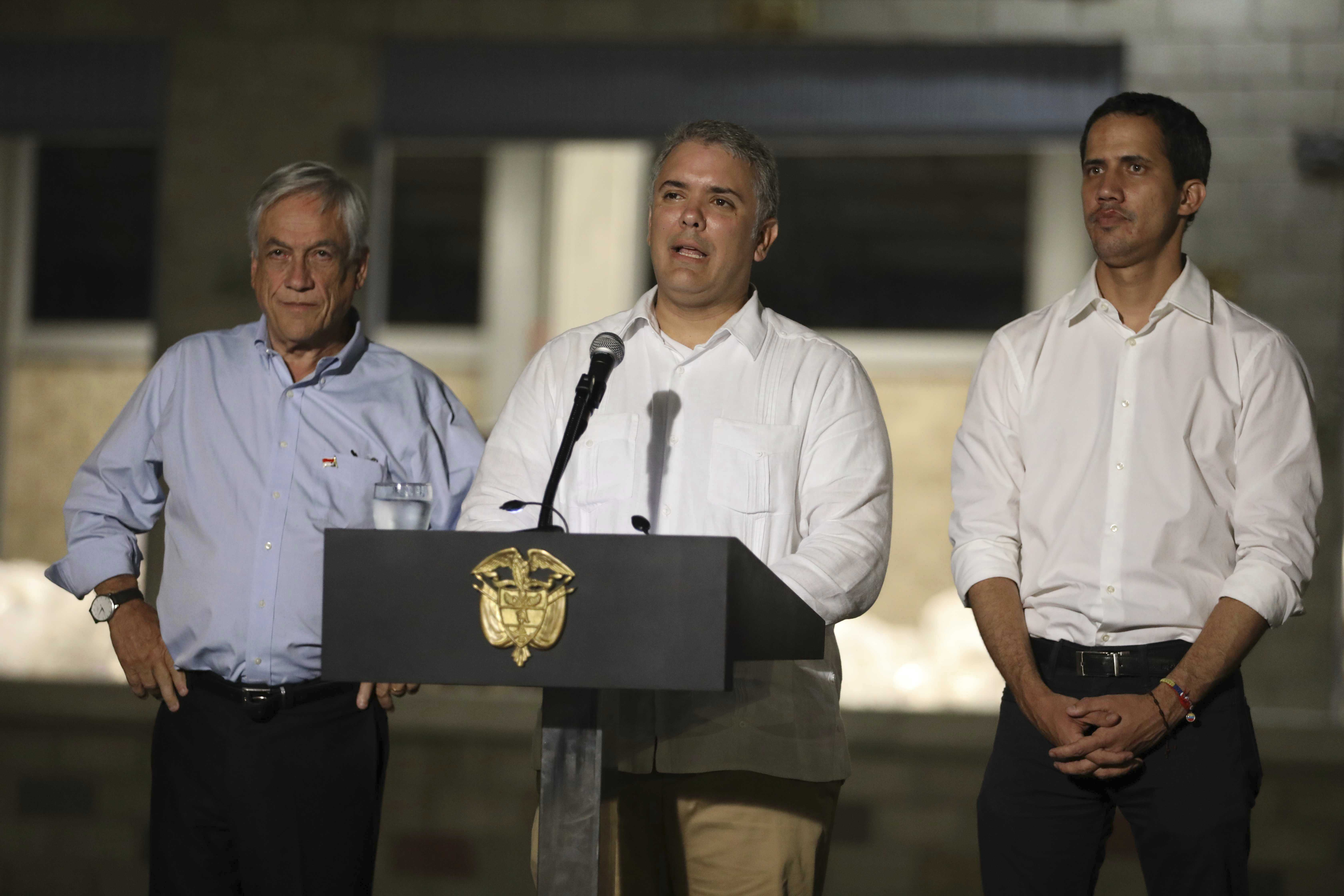 Colombia's President Ivan Duque, speaks flanked by Chile's President Sebastian Pinera, left, and Venezuela's self-proclaimed interim president Juan Guaido, in front of the warehouse housing U.S. humanitarian aid destined for Venezuela, in Cucuta, Colombia, Friday, Feb. 22, 2019. (AP Photo/Fernando Vergara)