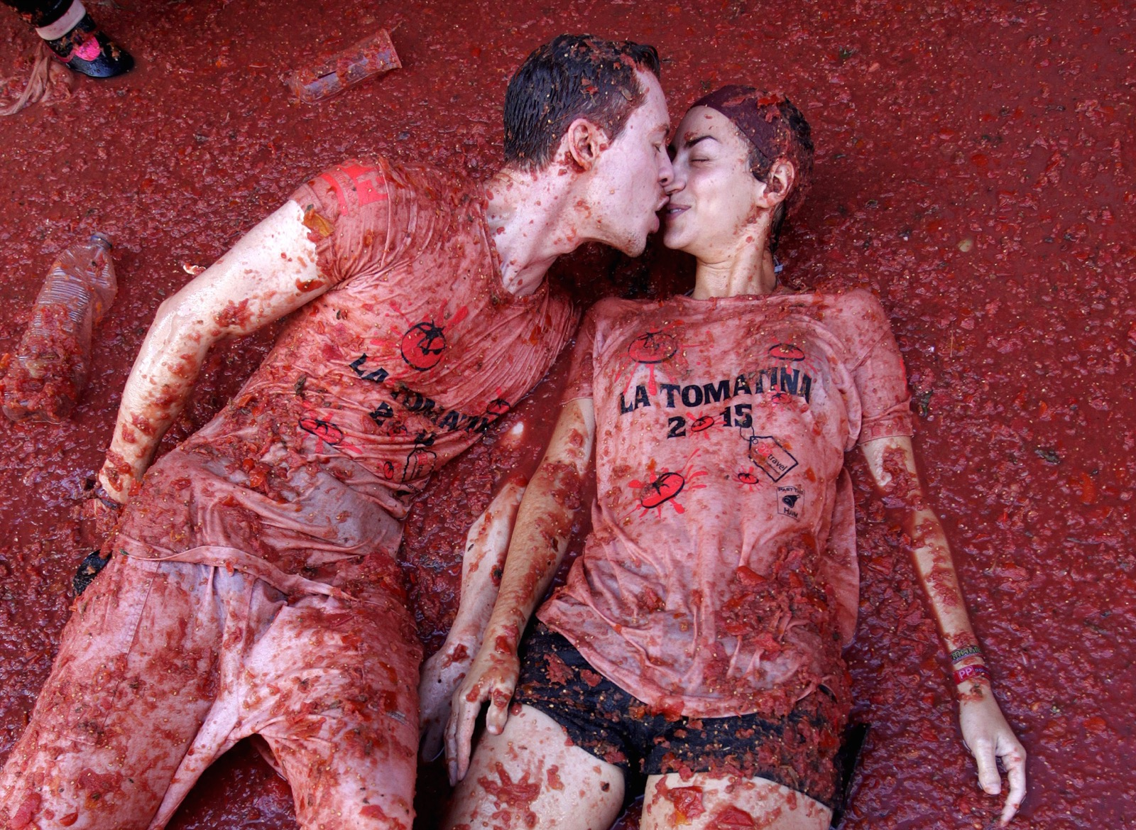 "Revelers kiss each other while lying in tomato pulp after the annual ""Tomatina"" (tomato fight) in Bunol, near Valencia, Spain, Wednesday. REUTERS/Heino Kalis"