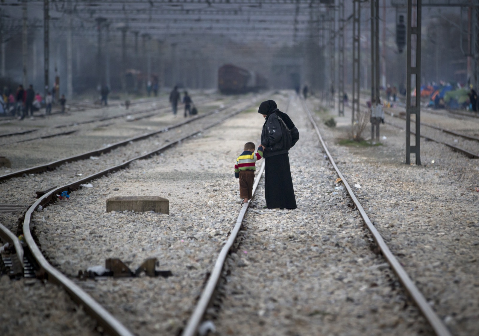 A woman holds the hand of a toddler walking on a railway track at the northern Greek border station of Idomeni. AP Photo/Vadim Ghirda