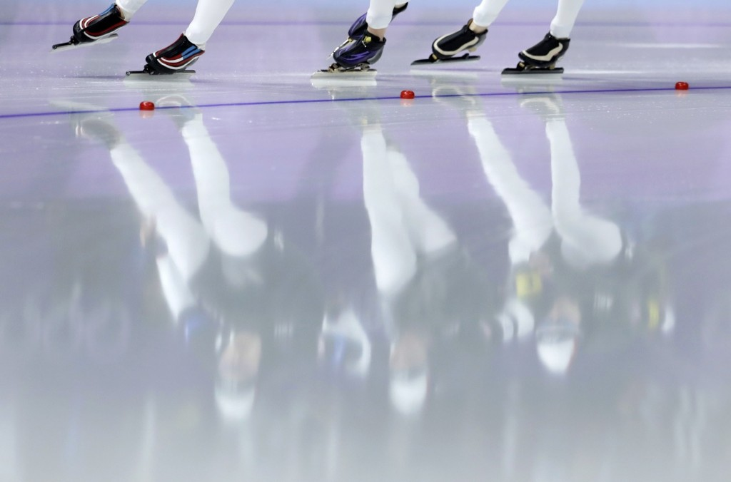Team USA with Heather Bergsma, Mia Manganello, and Carlijn Schoutens is reflected in the ice during the women's team pursuit semifinal speedskating race. AP Photo/Petr David Josek