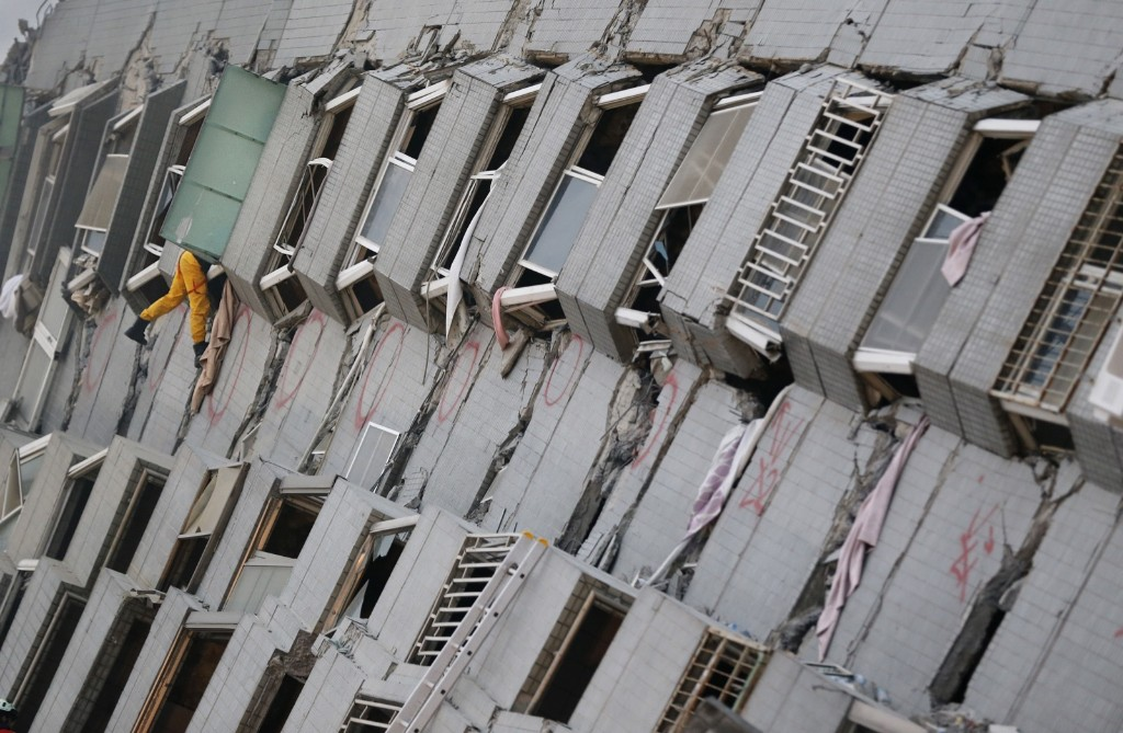 A rescue team member searches for missing people in a collapsed building. A 6.4-magnitude earthquake struck southern Taiwan early Saturday. AP Photo/Wally Santana