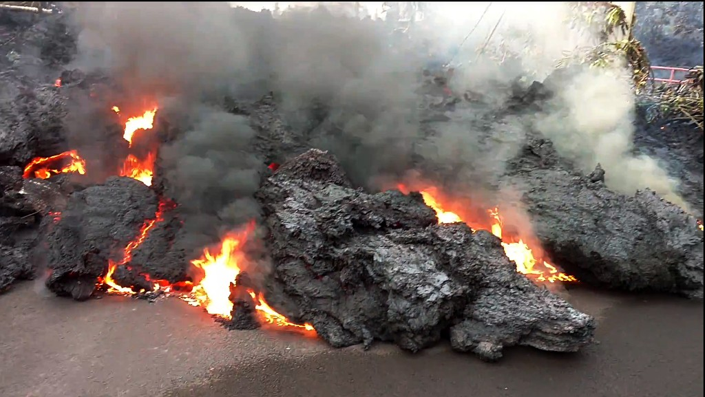 In this photo from video a lava flow advancing down a road is seen from less than 10 feet away in the Leilani Estates subdivision near Pahoa on the island of Hawaii Monday, May 7, 2018. Kilauea volcano has destroyed more than two dozen homes since it began spewing lava hundreds of feet into the air last week, and residents who evacuated don't know how long they might be displaced. The decimated homes were in the Leilani Estates subdivision, where molten rock, toxic gas and steam have been bursting through openings in the ground created by the volcano. (Scott Wiggers/Apau Hawaii Tours via AP)