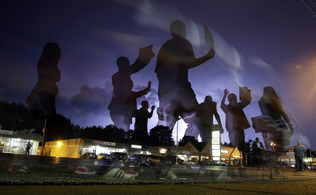 Protesters march as lightning flashes in the distance in Ferguson, Mo., Wednesday. AP Photo/Jeff Roberson