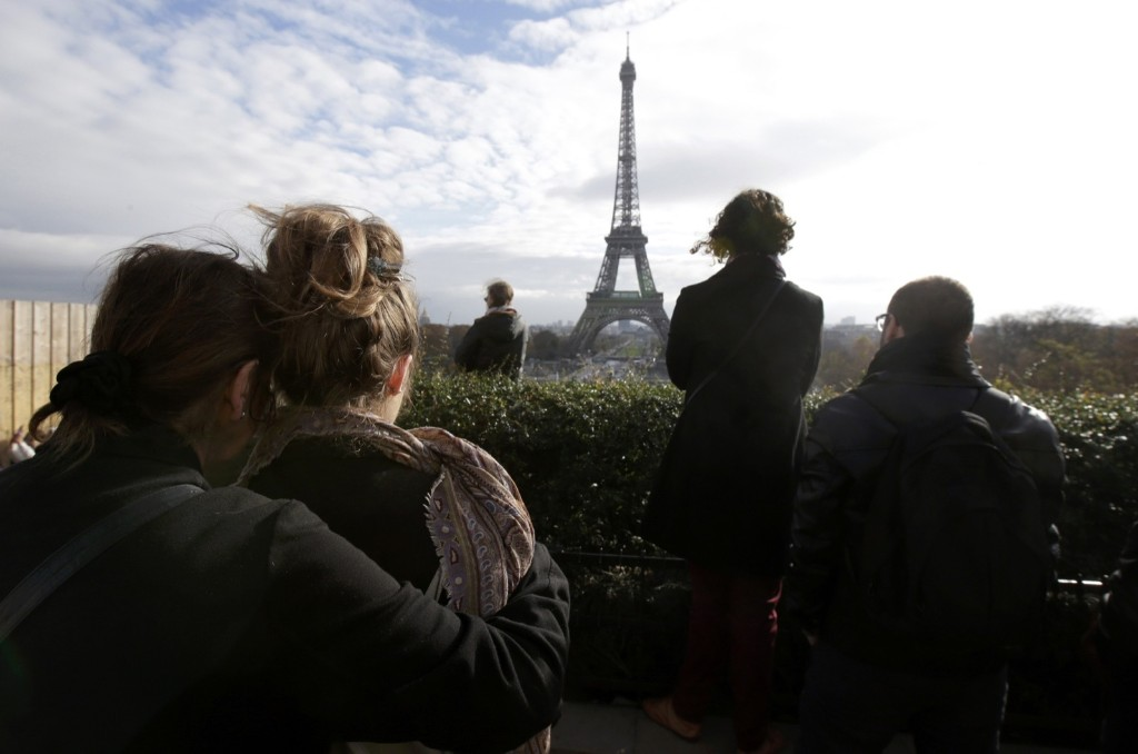 People observe a minute of silence at the Trocadero in front the Eiffel Tower to pay tribute to the victims of the series of deadly attacks in Paris, Monday. REUTERS/Philippe Wojazer