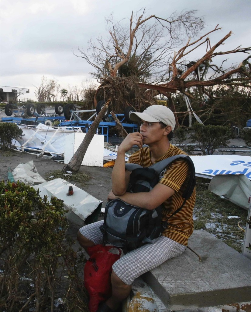 A survivor waits for a military mercy flight outside a damaged airport after super Typhoon Haiyan battered Tacloban city. REUTERS/Erik De Castro