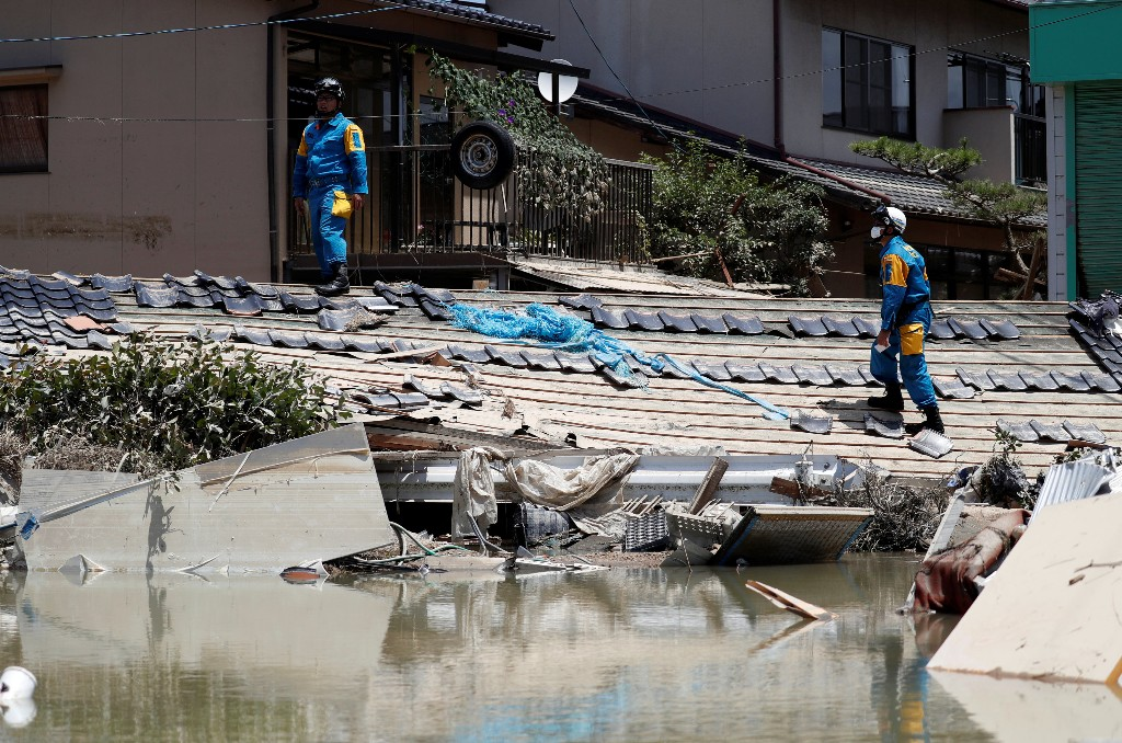 Police officers check submerged and destroyed houses in a flooded area in Mabi town in Kurashiki, Okayama Prefecture, Japan, July 10, 2018. REUTERS/Issei Kato