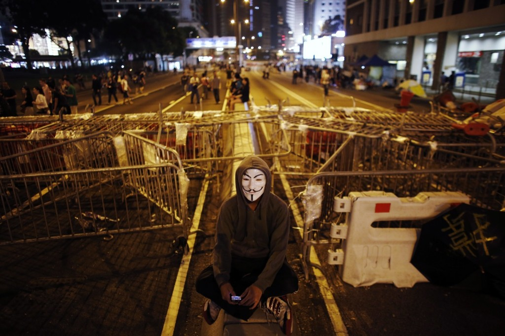 A protester sits in front of a barricade near the government headquarters building in Hong Kong. REUTERS/Carlos Barria