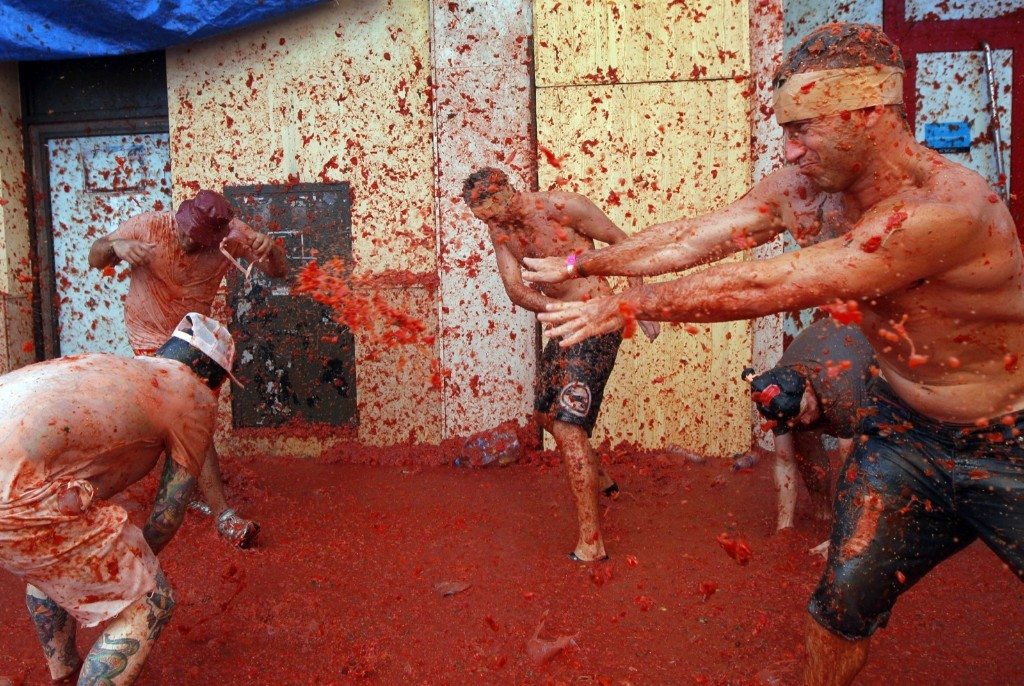 Men throw tomatoes at each other. AP Photo/Alberto Saiz