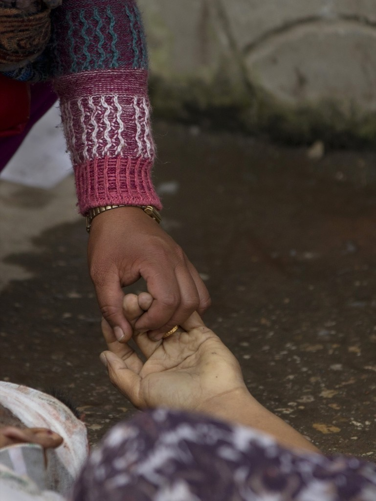 A Nepalese woman holds the hand of her relative killed in the earthquake in Kathmandu. AP Photo/Manish Swarup