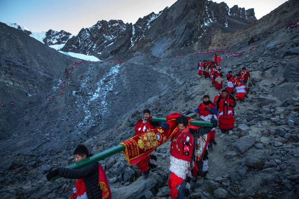 Pablitos descend a rock face carrying a cross after a ceremony on the glacier during the annual Qoyllur Rit'i festival in Ocongate, Peru. Every year, since 1783 in the Sinakara Valley at the foot of Mt. Ausagante, the Qoyllur Rit'i festival draws tens of thousands of pilgrims. Dan Kitwood/Getty Images