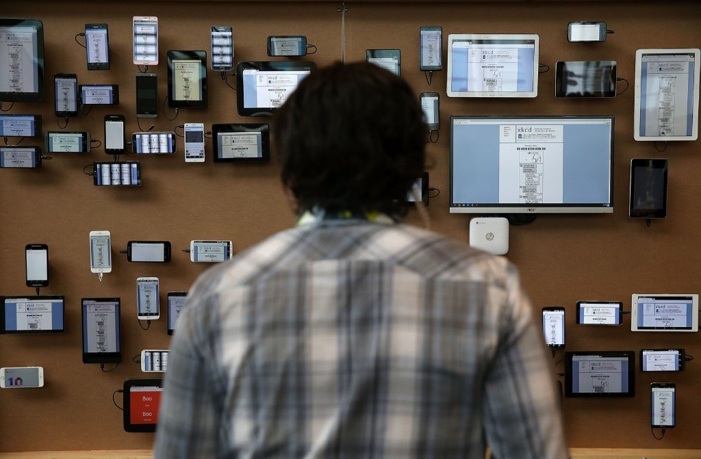 An attendee looks at a wall of devices during the 2015 Google I/O conference, Thursday, in San Francisco. Justin Sullivan/Getty Images