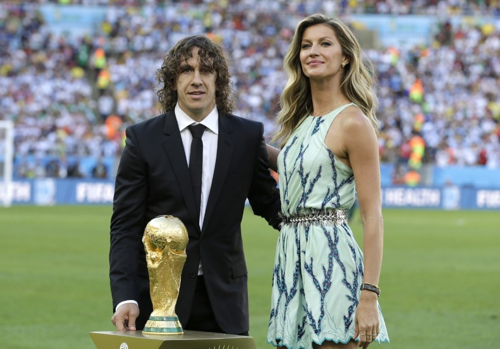 Former Spanish player Carles Puyol and model Gisele Bundchen stand next to the World Cup trophy before the World Cup final soccer match between Germany and Argentina at the Maracana Stadium in Rio de Janeiro, Brazil, July 13, 2014. AP Photo/Natacha Pisarenko