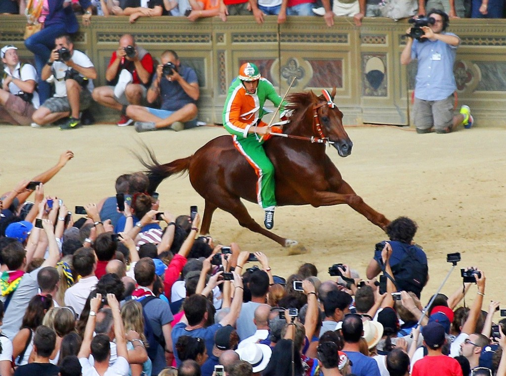 """Jockey Giovanni Atzeni of """"Selva"""" (Forest) parish on the horse """"Polonski"""", takes a curve on his way to win the Palio di Siena horse race in Siena August 17. REUTERS/Fabio Muzzi"""