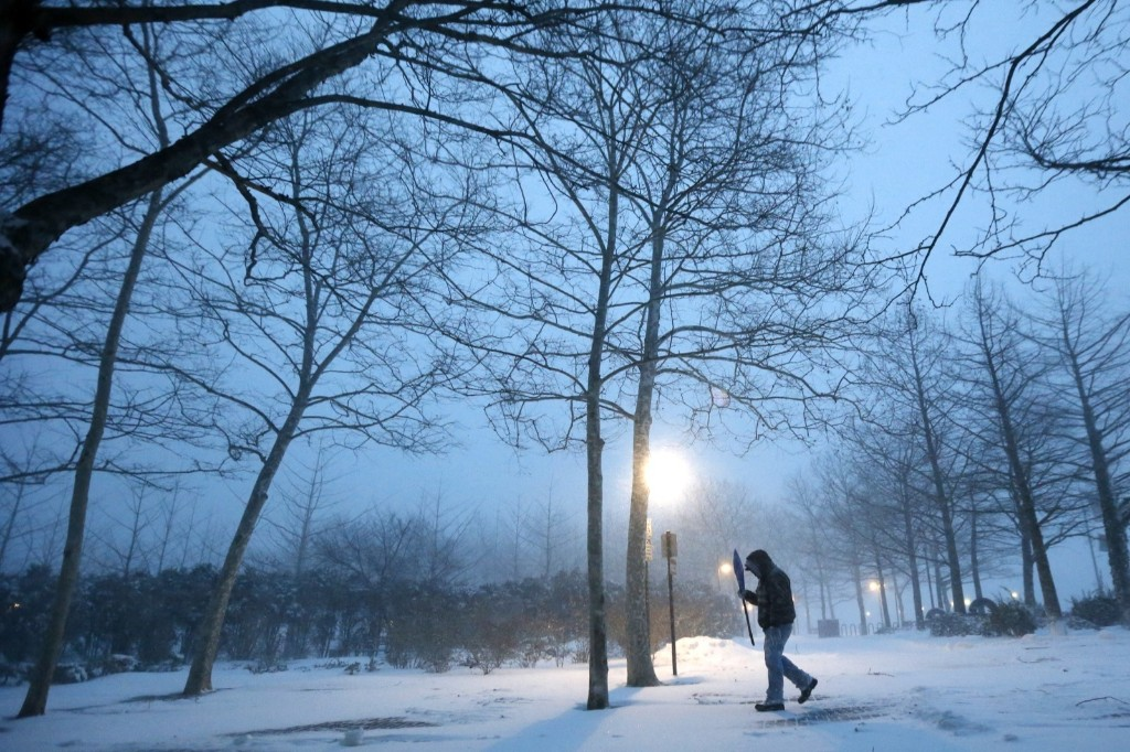 Hoboken city employee Edwin Lopez uses a snow shovel to block the sideways-blowing snow from his face while cleaning up a walking path at Pier A Park during snowstorm, Saturday, in Hoboken, N.J. AP Photo/Julio Cortez