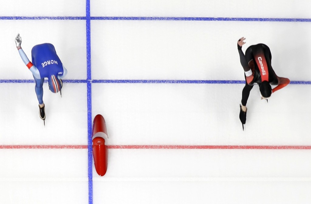 Ted-Jan Bloemen of Canada, right, crosses the finish line a fraction of a second before Norway's Sverre Lunde Pedersen during the men's 5000m speed skating race. AP Photo/Eugene Hoshiko