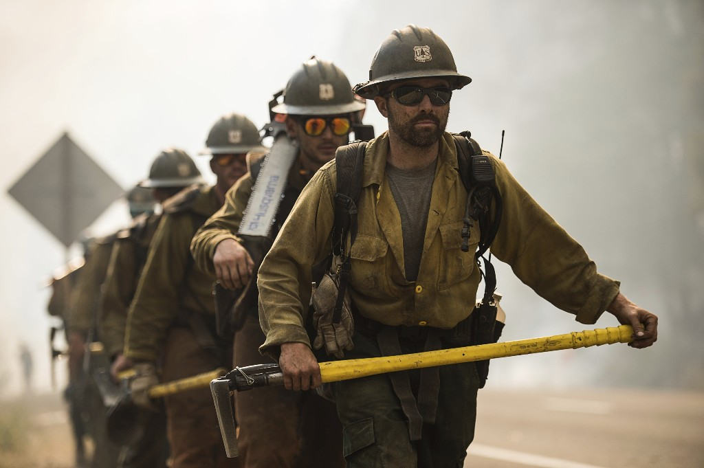 The El Dorado Hotshots battle wildfire near Buckhorn Summit on Highway 299 in Trinity County, Calif., Monday, July 30, 2018. A pair of wildfires that prompted evacuation orders for nearly 20,000 people barreled Monday toward small lake towns in Northern California, and authorities faced questions about how quickly they warned residents about the largest and deadliest blaze burning in the state. (Paul Kitagaki Jr./The Sacramento Bee via AP)