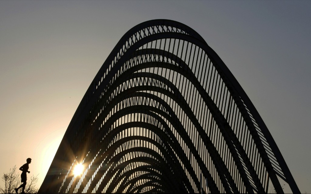 "A man jogs near the ""Agora"" structure at the Athens Olympic complex. REUTERS/Yannis Behrakis"