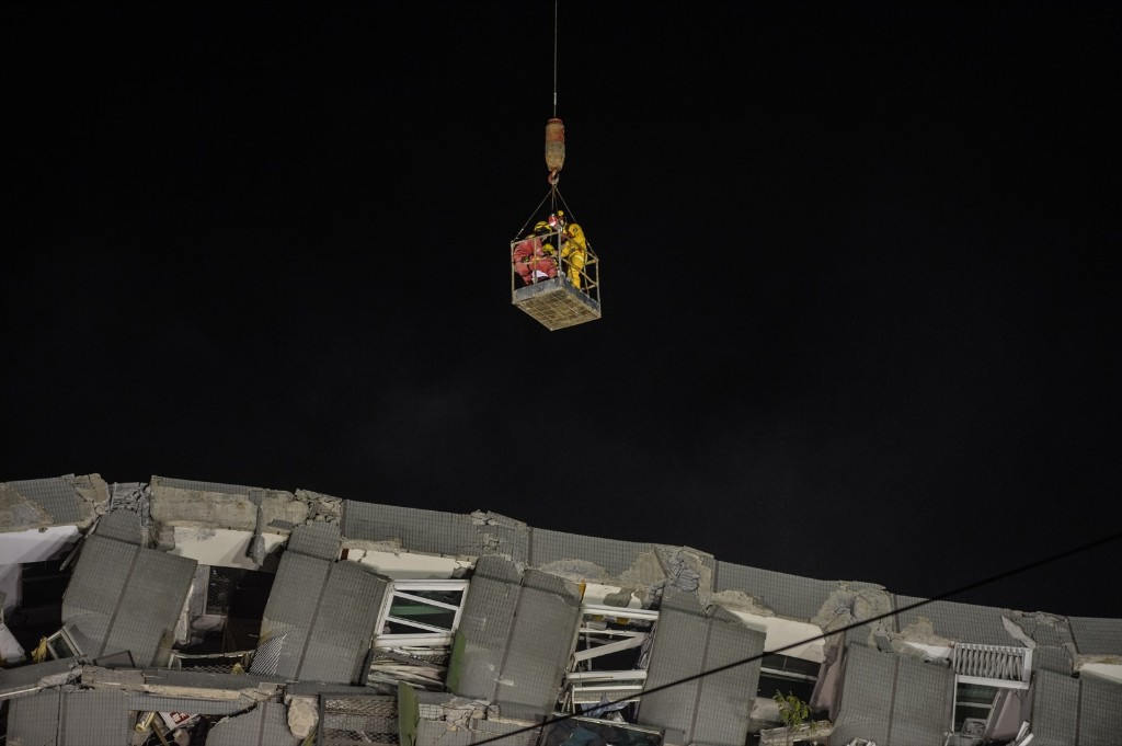 A woman is extracted by a crane from the rubble of a collapsed building. ANTHONY WALLACE/AFP/Getty Images