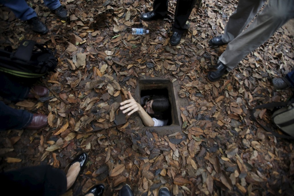 A French journalist tries to disappear into the Cu Chi tunnel network during a guided tour near Ho Chi Minh City. REUTERS/Kham