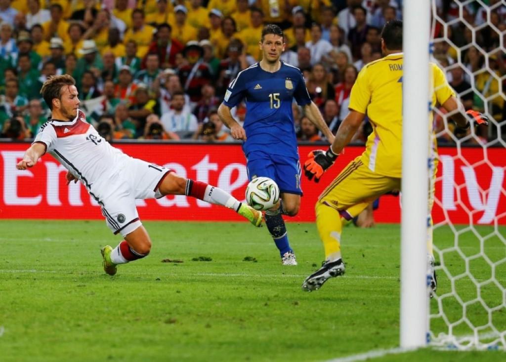 Germany's Mario Goetze shoots and scores past Argentina's goalkeeper Sergio Romero. REUTERS/Kai Pfaffenbach