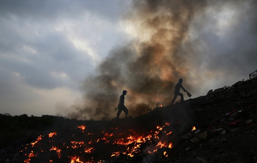 Impoverished Indians walk next to burning trash in Dharavi, one of the largest slums in Mumbai. AP Photo/Rafiq Maqbool