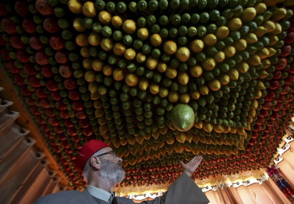 A member of the Samaritan sect decorates a traditional hut known as a sukkah with fruits and vegetables on Mount Gerizim near Nablus. REUTERS/Abed Omar Qusini