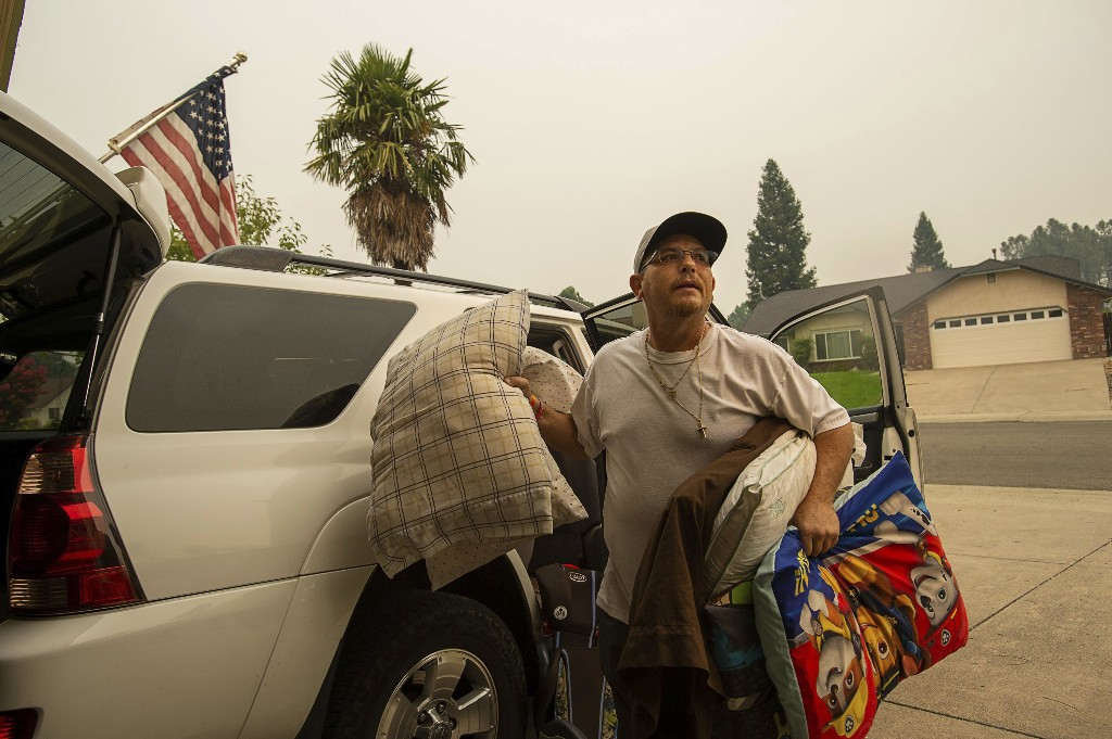 County Heights resident Kenny Campbell returns home after his neighbor was given the clear sign during the Carr Fire on Monday, July 30, 2018, in Redding, Calif. The California Department of Forestry and Fire Protection said people can return to several neighborhoods in western Redding as of Monday morning. (Paul Kitagaki Jr./The Sacramento Bee via AP)