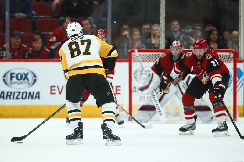 Jan 18, 2019; Glendale, AZ, USA; Pittsburgh Penguins center Sidney Crosby (87) shoots the puck to assist on the game winner in overtime against the Arizona Coyotes at Gila River Arena. Mandatory Credit: Mark J. Rebilas-USA TODAY Sports