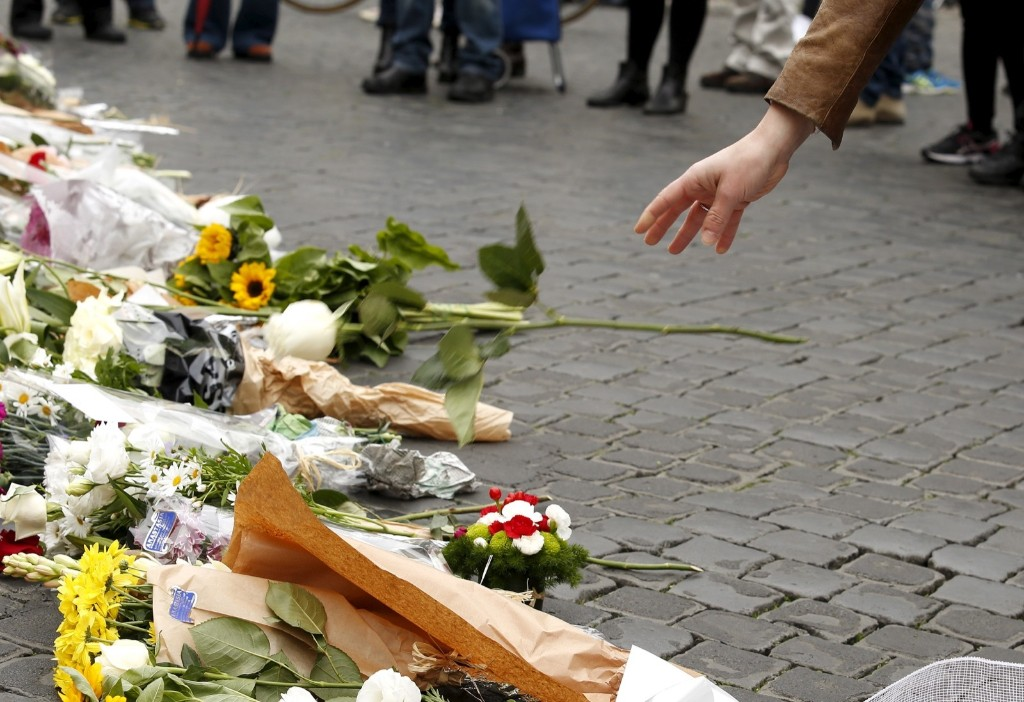 A woman places a flower, in sympathy with the victims of the Paris attacks, in front of the French embassy in Rome. REUTERS/Remo Casilli