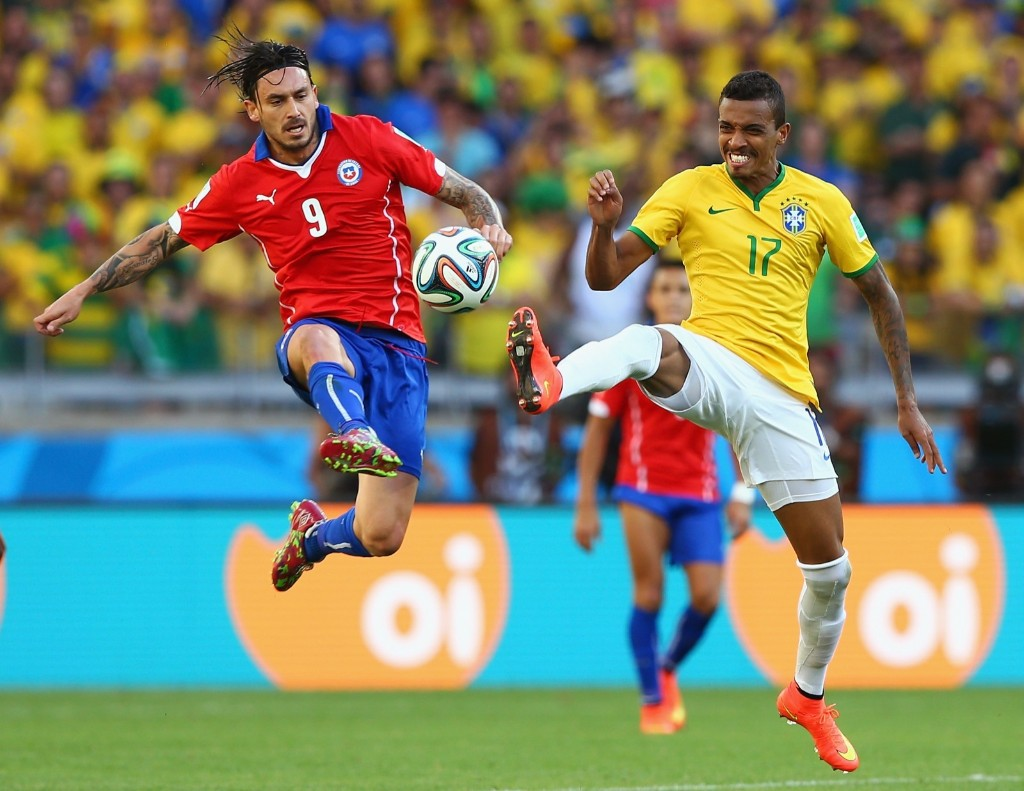Mauricio Pinilla of Chile and Luiz Gustavo of Brazil compete for ball. Quinn Rooney/Getty Images