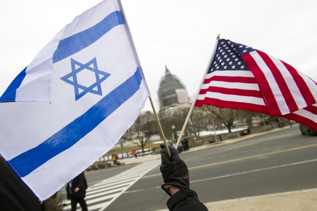 A pro-Israel demonstrator waves flags outside the U.S. Capitol in Washington, Tuesday, as Israeli Prime Minister Benjamin Netanyahu addressed a joint meeting of Congress. AP Photo/Cliff Owen