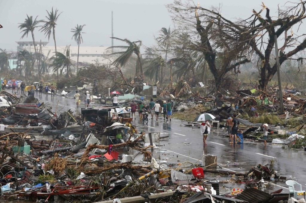 Residents walk on a road littered with debris in Tacloban. REUTERS/Erik De Castro