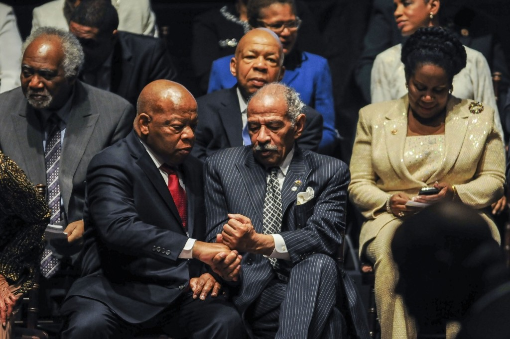 Rep. John Conyers gives Rep. John Lewis a fist bump during the Congressional Black Caucus swearing-in ceremony. Gabriella Demczuk/Getty Images