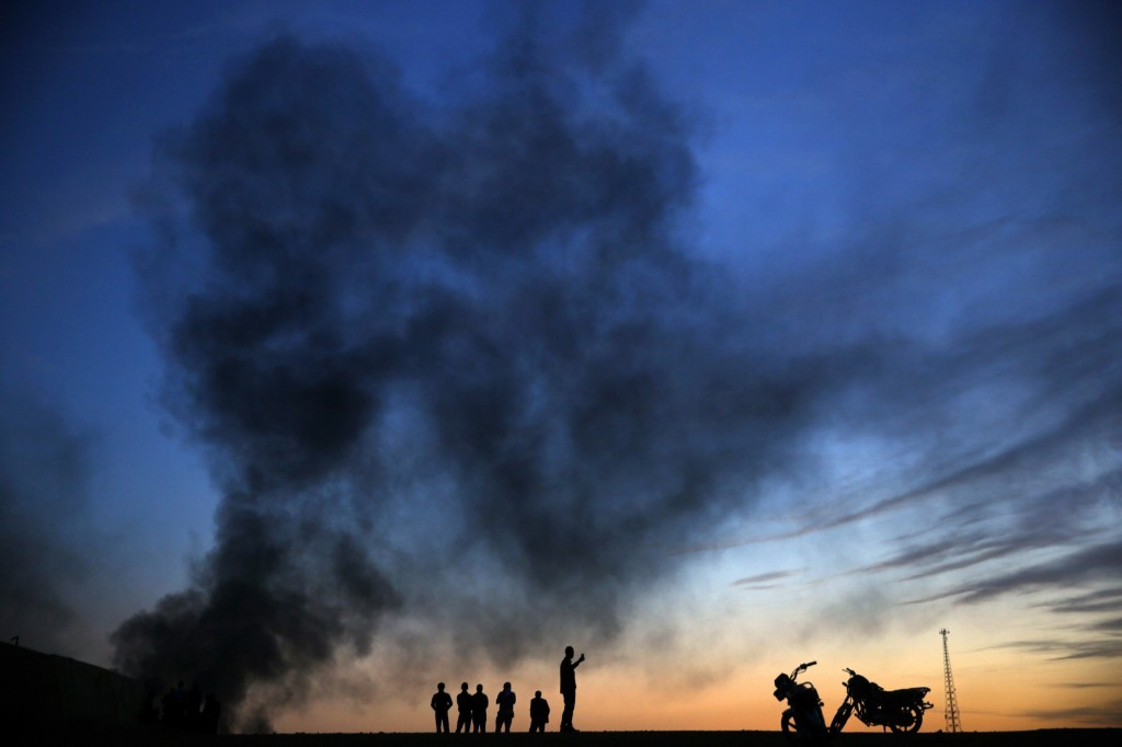Kurdish refugees walk on a hilltop as thick smoke rises from Kobani. REUTERS/Yannis Behrakis
