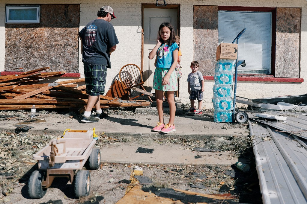 Hailey Strickland, 10, stands with her father Philip Strickland and her brothers as they carry water into their home in the aftermath of Hurricane Michael in Parker, Florida, U.S., October 13, 2018. REUTERS/Terray Sylvester