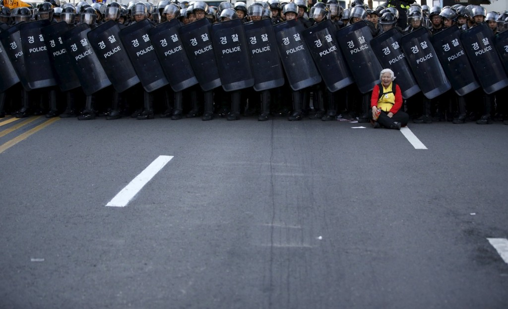 An elderly protester yells as she is blocked by a barricade of policemen while marching down the street during a rally in central Seoul. REUTERS/Kim Hong-Ji