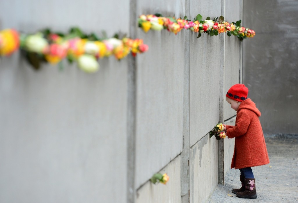 A young girl slips a rose in a preserved segment of the Berlin Wall during 25th anniversary commemorations, Nov. 9. JOHN MACDOUGALL/AFP/Getty Images