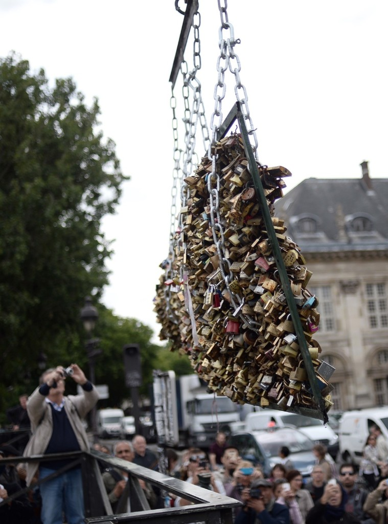 "People take photographs as workers remove panels bearing ""love padlocks"" attached on the railings of the Pont des Arts bridge in Paris, Monday. Stephane de Sakutin/AFP/Getty Images"