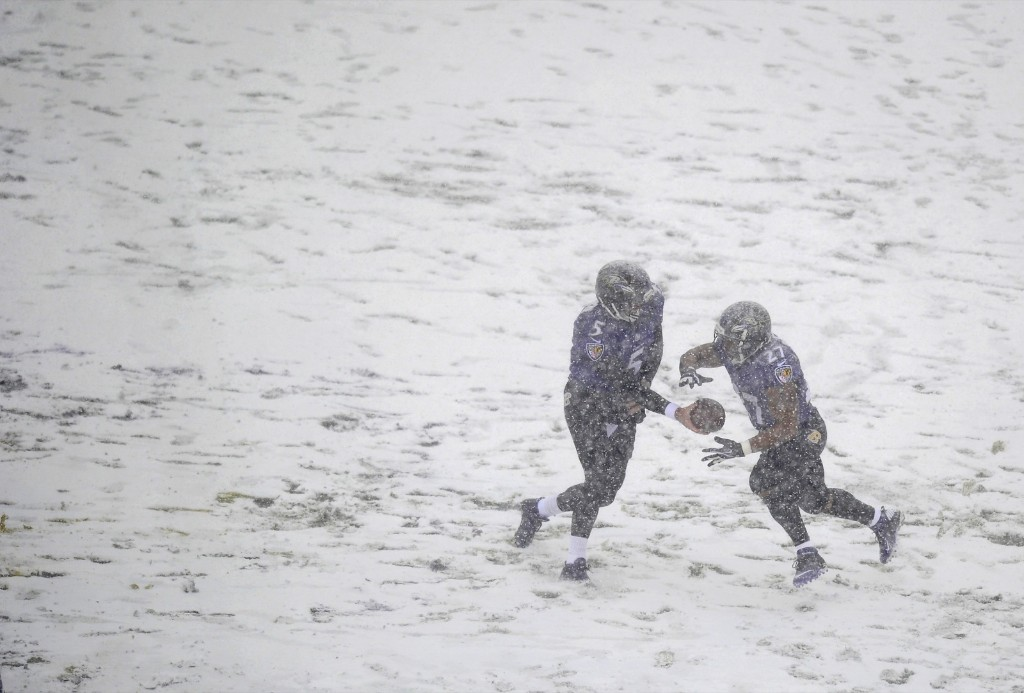 Ravens quarterback Joe Flacco hands ball off to Ray Rice as snow falls in Baltimore. AP Photo/Nick Wass
