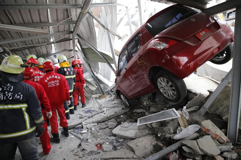 Rescue workers search a collapsed building from an early morning earthquake. AP Photo/Wally Santana